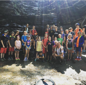 A group of 30 young students and the trip leader standing near a creek and rocky wall.
